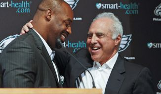 FILE - In this July 29, 2013, file photo, six-time Pro Bowl quarterback Donovan McNabb, left, and Philadelphia Eagles owner Jeffrey Lurie embrace following a news conference in Philadelphia, where it was announced that McNabb was to officially retire as a member of the Eagles. McNabb played 11 of his 13 seasons with the Eagles, leading them to eight playoff appearances, five NFC East titles, five conference championship games and one Super Bowl loss. Lurie grew up a passionate Boston sports fan. He even tried to buy the Patriots in 1993 but was outbid by Robert Kraft. So the former movie producer paid $195 million for the Eagles in 1994. Lurie vowed to win multiple championships for a city that hasn't celebrated an NFL title since 1960.He's still waiting for No. 1. Nothing else matters this week. (AP Photo/ Joseph Kaczmarek, File)