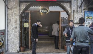 """Restaurant workers and police stand following a rocket attack, fired from inside Syria, in the border town of Kilis, Turkey, Thursday, Feb. 1, 2018. Kilis and the town of Reyhanli, both of which border Afrin, Syria, have been the target of multiple rocket attacks that have killed at least four people, including a teenage girl and injured dozens of others. Turkey launched a cross-border offensive into Afrin on Jan. 20 to clear the enclave of Syrian Kurdish militia which Ankara considers to be """"terrorists."""" (Can Erok/DHA-Depo Photos via AP)"""