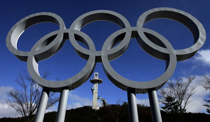 The tower for the Alpensia Ski Jumping Center rises beyond a set of Olympic Rings at the 2018 Winter Olympics in Pyeongchang, South Korea, Friday, Feb. 2, 2018. (AP Photo/Charlie Riedel)