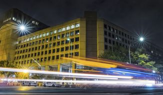 Traffic along Pennsylvania Avenue in Washington, D.C., streaks past the FBI headquarters building on Nov. 1, 2017. (Associated Press) **FILE**