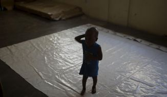 A boy stands on a tarp at the Foyer Notre Dame de la Nativite orphanage on the outskirts of Port-au-Prince, Haiti, Friday, Feb. 2, 2018. The State Department is being urged by a group of U.S. senators to pressure the Haitian government into closing the orphanage where several children being adopted by U.S. families have been victims of alleged sexual abuse. (AP Photo/Dieu Nalio Chery)