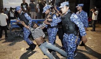 Maldivian police officers detain an opposition protestor demanding the release of political prisoners during a protest in Male, Maldives, Friday, Feb. 2, 2018. Supporters of political parties that oppose the Maldives government have clashed with police on the streets of the capital after the country's supreme court ordered the release of imprisoned politicians. (AP Photo/Mohamed Sharuhaan)