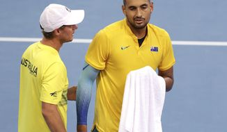 Nick Kyrgios of Australia, right, talks with his team captain Lleyton Hewitt, left in his match against Jan-Lennard Struff of Germany at the Davis Cup World Group first round in Brisbane, Australia, Friday, Feb.2, 2018. (AP Photo/Tertius Pickard)
