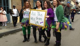 A group of women pose with a sign on Royal Street in the French Quarter on Friday, Feb. 2, 2018, as the two big weekends ahead of Mardi Gras kick off in New Orleans. (AP Photo/Stacey Plaisance)