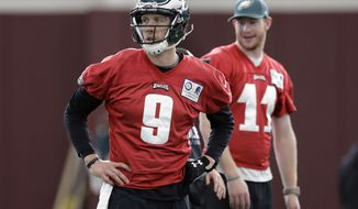 Injured Philadelphia Eagles quarterback Carson Wentz (11) looks on as quarterback Nick Foles (9) takes part a practice for the NFL Super Bowl 52 football game Thursday, Feb. 1, 2018, in Minneapolis. Philadelphia is scheduled to face the New England Patriots Sunday. (AP Photo/Eric Gay)