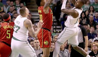 Boston Celtics guard Terry Rozier (12) looks to pass to forward Daniel Theis (27) as Atlanta Hawks forward John Collins (20) defends during the first half of an NBA basketball game Friday, Feb. 2, 2018, in Boston. (AP Photo/Mary Schwalm)