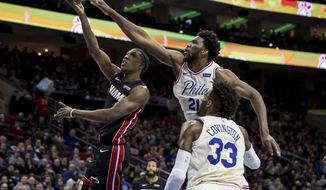 Miami Heat's Josh Richardson, left, shoots as Philadelphia 76ers' Joel Embiid, center, defends while Robert Covington, right, watches during the first half of an NBA basketball gam  Friday, Feb. 2, 2018, in Philadelphia. (AP Photo/Chris Szagola)