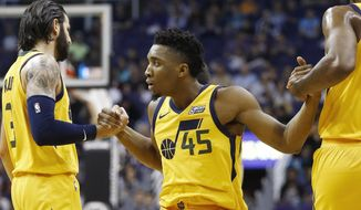 After being fouled on a 3-point basket, Utah Jazz guard Donovan Mitchell (45) is helped up off the floor by guards Ricky Rubio (3) and Joe Johnson, right, during the first half of an NBA basketball game Friday, Feb. 2, 2018, in Phoenix. (AP Photo/Ross D. Franklin)