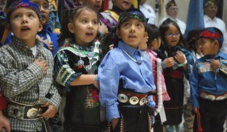 Children from Zuni Pueblo lead the U.S. pledge of allegiance in the Zuni language in the New Mexico state Capitol in Santa Fe, N.M., on Friday, Feb. 2, 2018. Head Start program teacher Rylan Chimoni helps the children learn their tribal language at an early age. The Legislature held an annual celebration of indigenous communities and culture.(AP Photo/Morgan Lee)