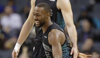 Charlotte Hornets' Frank Kaminsky, back, and Kemba Walker celebrate during a timeout in the first half of the team's NBA basketball game against the Indiana Pacers in Charlotte, N.C., Friday, Feb. 2, 2018. (AP Photo/Chuck Burton)