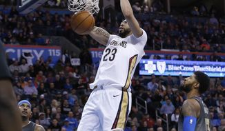 New Orleans Pelicans forward Anthony Davis (23) dunks between Oklahoma City Thunder forward Carmelo Anthony (7) and center Steven Adams (12) during the first half of an NBA basketball game in Oklahoma City, Friday, Feb. 2, 2018. (AP Photo/Sue Ogrocki)