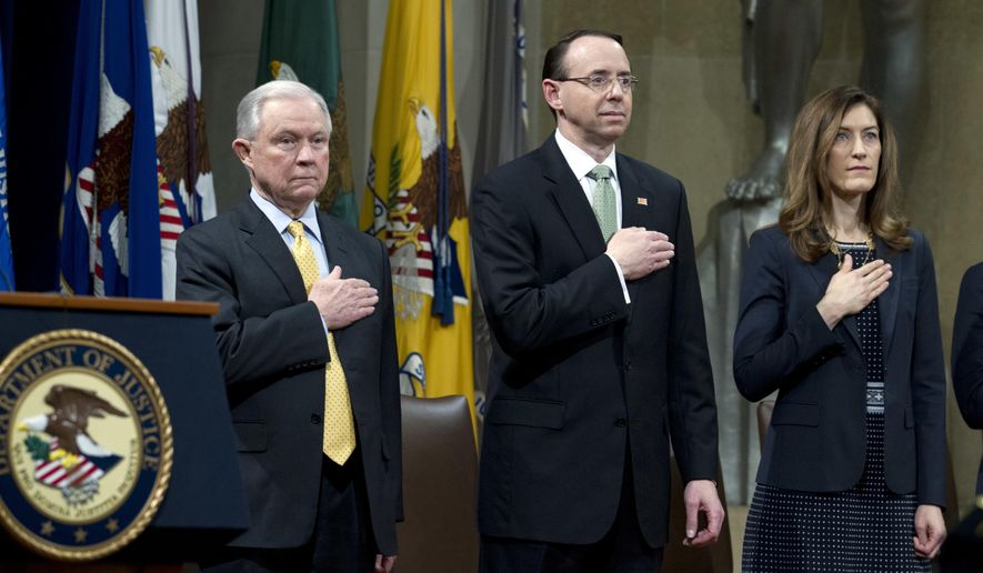 Attorney General Jeff Sessions accompanied by Deputy Attorney General Rod Rosenstein and Associate Attorney General Rachel Brand, listen the national anthem during the opening ceremony of the summit on Efforts to Combat Human Trafficking at Department of Justice in Washington, Friday, Feb. 2, 2018. President Donald Trump, dogged by an unrelenting investigation into his campaign's ties to Russia, lashes out at the FBI and Justice Department as politically biased ahead of the expected release of a classified Republican memo criticizing FBI surveillance tactics.   (AP Photo/Jose Luis Magana)
