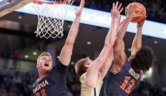 FILE - In this Thursday, Jan. 18, 2018, file photo, Georgia Tech center Ben Lammers (44) battles Virginia's De'Andre Hunter (12) and Jack Salt (33) for a rebound during the first half of an NCAA college basketball game in Atlanta. The Cavaliers lead the nation in scoring defense, allowing 52.7 points per game. (AP Photo/John Bazemore, File)