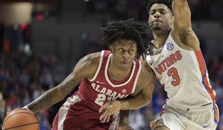Alabama guard John Petty (23) dribbles past Florida guard Jalen Hudson (3) during the first half of an NCAA college basketball game in Gainesville, Fla., Saturday, Feb. 3, 2018. (AP Photo/Ron Irby)