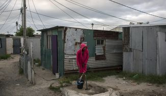 """A woman collects water in a settlement near Cape Town on Friday, Feb. 2, 2018. South Africa's drought-hit city of Cape Town introduced new water restrictions in an attempt to avoid what it calls """"Day Zero,"""" the day in mid-April when it might have to turn off most taps. (AP Photo/Bram Janssen)"""
