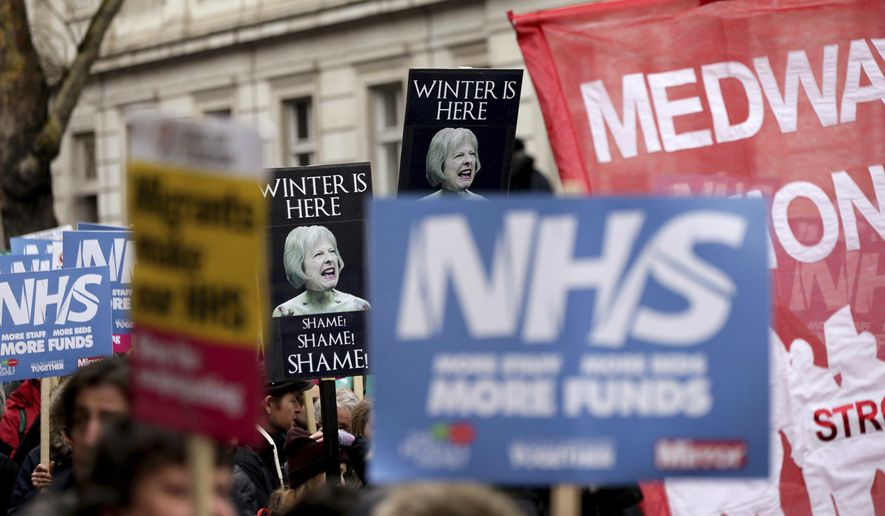 People wave banners depicting Britain's Prime Minister Theresa May, during a protest march in support of the National Health Service (NHS), as winter conditions are thought to have put severe strain on health services, in London Saturday Feb. 3, 2018.  The Government is urged to provide funds for beds and staff to ease the problems facing the NHS medical services. (Yui Mok/PA via AP)
