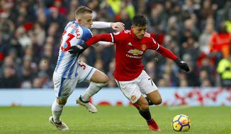 Huddersfield Town's Florent Hadergjonaj, left, and Manchester United's Alexis Sanchez during their English Premier League soccer match at Old Trafford in Manchester, England, Saturday Feb. 3, 2018. (Martin Rickett/PA via AP)