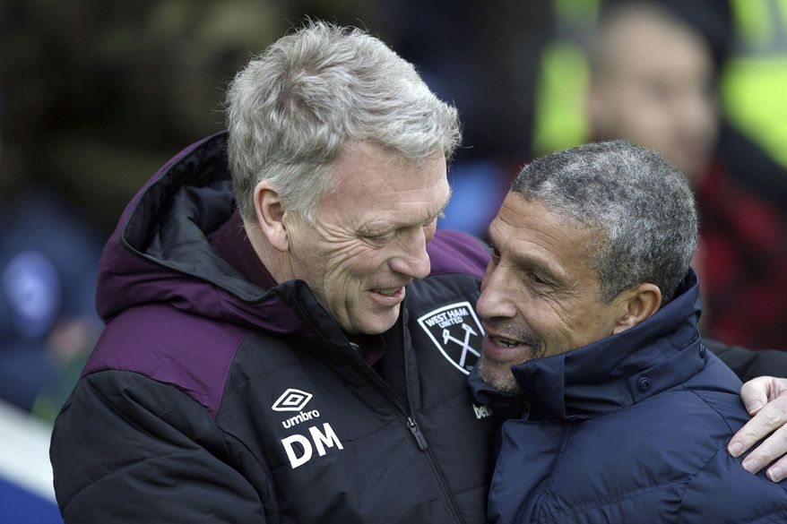 West Ham United manager David Moyes, left and Brighton & Hove Albion manager Chris Hughton hug prior to the English Premier League soccer match between Brighton and West Ham United, at the AMEX Stadium, in Brighton, England,  Saturday, Feb. 3, 2018. (Steven Paston/PA via AP)