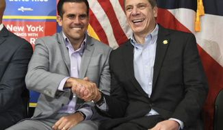 "In this photo provided by New York Gov. Andrew Cuomo's office, Puerto Rico's Gov. Ricardo Rossello, left, shakes hands with Cuomo at a rally in the Bronx borough of New York, Saturday, Feb. 4, 2018. At the event, Cuomo stated that he was ""ashamed"" that this country failed to help Puerto Rico recover faster from last year's hurricane. About a third of Puerto Rico remains without power. (New York Governor's Office via AP)"