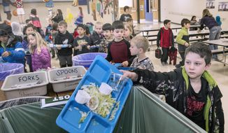 In a Jan. 26, 2018 photo, first-grader Alex Mundil dumps his tray into the composting bin after finishing lunch at Maxey Elementary School in Lincoln, Neb. The efforts at Maxey are just a piece of Lincoln Public Schools' efforts at sustainability. One of the programs that's grown considerably is composting, composting the waste from many of the 4.6 million lunches and 1.3 million breakfasts it serves.  (Eric Gregory/The Journal-Star via AP)