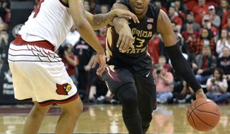 Florida State guard M.J. Walker (23) attempts to drive past the defense of Louisville guard Quentin Snider (4) during the first half of an NCAA college basketball game, Saturday, Feb. 3, 2018, in Louisville, Ky. (AP Photo/Timothy D. Easley)