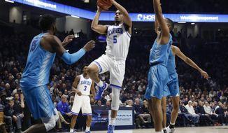 Xavier's Trevon Bluiett (5) shoots over Georgetown's Jessie Govan (15) during the first half of an NCAA college basketball game Saturday, Feb. 3, 2018, in Cincinnati. (AP Photo/John Minchillo)