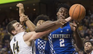 Kentucky's Jarred Vanderbilt, right, Nick Richards, centers and Missouri's Reed Nikko, left, battle for rebound during the first half of an NCAA college basketball game Saturday, Feb. 3, 2018, in Columbia, Mo. (AP Photo/L.G. Patterson)