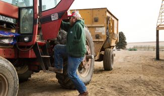Kyle Lammers climbs into his tractor to feed cattle Friday, Jan 19, 2018, in Hartington, Neb. In November of 1998, Lammers lost his left arm in a farming accident when he was 13 years old. (Ryan Soderlin/The World-Herald via AP)