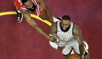Cleveland Cavaliers' LeBron James, right, drives to the basket against Houston Rockets' James Harden in the first half of an NBA basketball game, Saturday, Feb. 3, 2018, in Cleveland. (AP Photo/Tony Dejak)