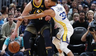 Denver Nuggets center Nikola Jokic, left, tries to move the ball as Golden State Warriors guard Stephen Curry defends in the first half of an NBA basketball game Saturday, Feb. 3, 2018, in Denver. (AP Photo/David Zalubowski)