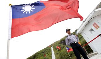 A Taiwan Coast Guard officer stands guard under a Taiwanese flag during Taiwanese President Ma Ying-jeou's visit to Pengjia Islet in the East China Sea, north of Taiwan, Saturday, April 9, 2016. Ma visited the small island to reassert Taiwan's sovereignty and its role in the contested region, one of the key issues of his administration that ends next month. Ma's visit to Pengjia, roughly 35 miles (56 kilometers) north of Taiwan proper, was his administration's second propaganda trip to an island in three weeks. It came four years after Ma last visited Pengjia to propose a plan to address territorial disputes between China, Taiwan and Japan over the nearby chain known as Senkaku in Japanese and Diaoyutai in Chinese. (AP Photo/Chiang Ying-ying)