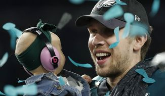 Philadelphia Eagles' Nick Foles holds his daughter, Lily, after the NFL Super Bowl 52 football game against the New England Patriots, Sunday, Feb. 4, 2018, in Minneapolis. The Eagles won 41-33. (AP Photo/Matt York)