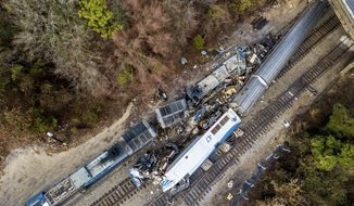 An aerial view of the site of an early morning train crash Sunday, Feb. 4, 2018, between an Amtrak train, bottom right, and a CSX freight train, top left, in Cayce, S.C. The Amtrak passenger train slammed into a freight train in the early morning darkness Sunday, killing at least two Amtrak crew members and injuring more than 110 people, authorities said. (AP Photo/Jeff Blake)