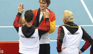 Alexander Zverev of Germany, center, celebrates with his team after he won his match against Nick Kyrgios of Australia at the Davis Cup World Group first round in Brisbane, Australia, Sunday, Feb. 4, 2018. (AP Photo/Tertius Pickard)