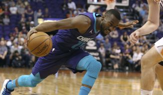 CORRECTS TO SUNDAY NOT SATURDAY - Charlotte Hornets guard Kemba Walker, left, drives to the basket as Phoenix Suns' Dragan Bender defends during the first half of an NBA basketball game Sunday, Feb. 4, 2018, in Phoenix. (AP Photo/Ralph Freso)