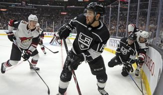 Los Angeles Kings center Alex Iafallo (19) clears the puck from the corner during the second period of the team's NHL hockey game against the Arizona Coyotes in Los Angeles on Saturday, Feb. 3, 2018. (AP Photo/Reed Saxon)