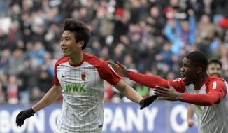 Augsburg's scorer Koo Ja-cheol, left, and Kevin Danso celebrate after the opening goal, during the German Bundesliga soccer match between FC Augsburg and Eintracht Frankfurt, in Augsburg, Germany, Sunday, Feb. 4, 2018. (Stefan Puchner/dpa via AP)