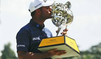 India's Shubhankar Sharma kisses his trophy after winning the Maybank Championship golf tournament in Shah Alam, Malaysia, Sunday, Feb. 4, 2018. (AP Photo/Sadiq Asyraf)