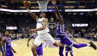 Dallas Mavericks guard Dennis Smith Jr., center, goes to the basket past Sacramento Kings forward JaKarr Sampson, right, during the first half of an NBA basketball game Saturday, Feb. 3, 2018, in Sacramento, Calif. (AP Photo/Rich Pedroncelli)