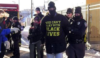 Protesters chained themselves to fences and to each other to form a human blockade along light rail tracks at the West Bank Station in Minneapolis near U.S. Bank Stadium prior to the start of Super Bowl LII on Sunday, Feb. 4, 2018, in Minneapolis, Minn. Activists in Minnesota are using the spectacle of the Super Bowl to speak out against police brutality, racism, corporate greed and other issues. (David Joles/Star Tribune via AP)