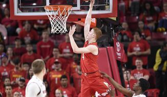 Maryland guard Kevin Huerter (4) goes to the basket against Wisconsin guard Khalil Iverson, bottom right, during the first half of an NCAA basketball game, Sunday, Feb. 4, 2018, in College Park, Md. (AP Photo/Nick Wass)