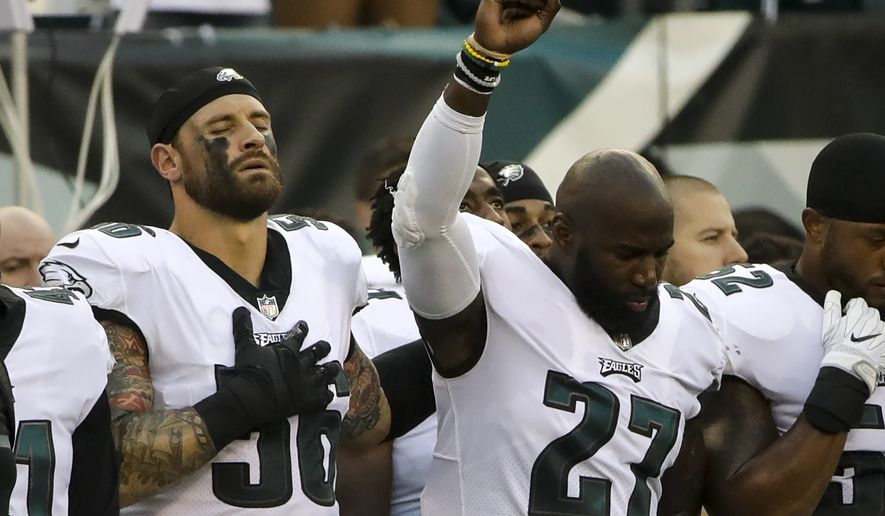 Philadelphia Eagles' Chris Long (56) stands beside Malcolm Jenkins (27) as he raises his fist during the national anthem before the team's NFL preseason football game against the Buffalo Bills, Thursday, Aug. 17, 2017, in Philadelphia. (AP Photo/Matt Rourke)