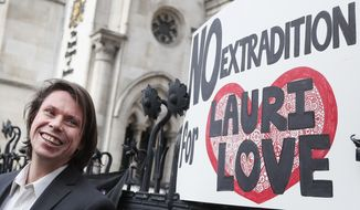 Lauri Love smiles outside The Royal Courts of Justice in London, Monday, Feb. 5, 2018. The ruling in Lauri Love's appeal against extradition to the United States, where he faced solitary confinement and a potential 99 year prison sentence, was ruled in his favour on Monday Feb. 5 at the Royal Courts of Justice.(AP Photo/Kirsty Wigglesworth)