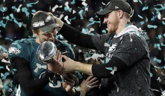 Philadelphia Eagles quarterback Carson Wentz, right, hands the Vincent Lombardi trophy to Nick Foles after winning the NFL Super Bowl 52 football game against the New England Patriots, Sunday, Feb. 4, 2018, in Minneapolis. The Eagles won 41-33. (AP Photo/Frank Franklin II)