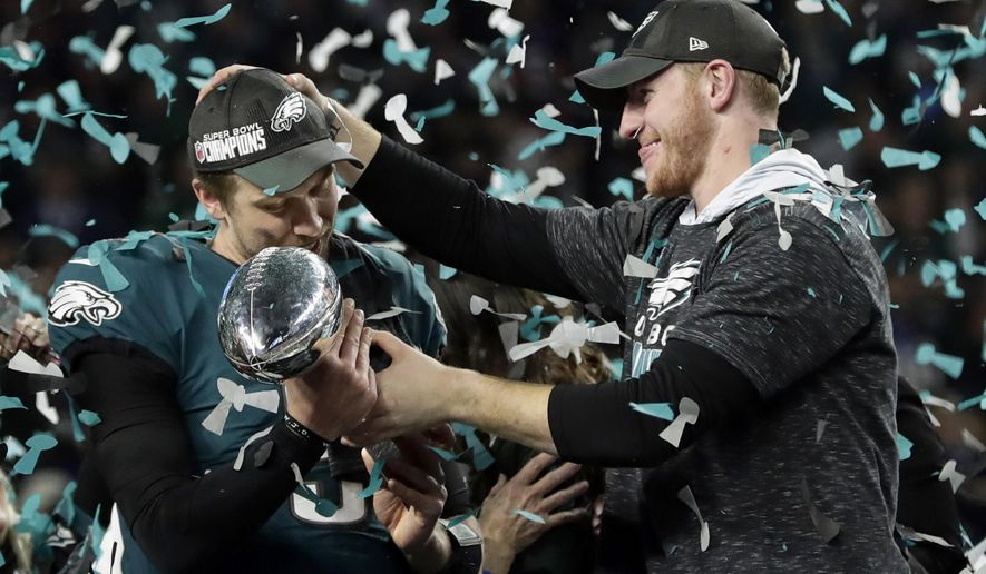 Philadelphia Eagles quarterback Carson Wentz, right, hands the Vincent Lombardi trophy to Nick Foles after winning the NFL Super Bowl 52 football game against the New England Patriots, Sunday, Feb. 4, 2018, in Minneapolis. The Eagles won 41-33. (AP Photo/Frank Franklin II) ** FILE **