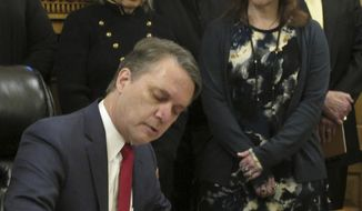 Kansas Gov. Jeff Colyer signs an executive order on sexual harassment as members of his Cabinet watch, Monday, Feb. 5, 2018, at the Statehouse in Topeka, Kan. The order requires thousands of executive branch employees to undergo annual sexual harassment training, (AP Photo/John Hanna)