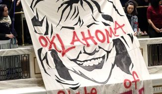 "Protestors raise a banner with the message ""Oklahoma State of Despair"" during Gov. Mary Fallin's State of the State speech at the State Capitol in Oklahoma City, Okla., Monday, Feb. 5, 2018. (Matt Barnard/Tulsa World via AP)"