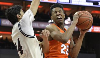 Syracuse guard Tyus Battle (25) goes up to shoot past the defense of Louisville forward Anas Mahmoud (14) during the first half of an NCAA college basketball game, Monday, Feb. 5, 2018, in Louisville, Ky. (AP Photo/Timothy D. Easley)
