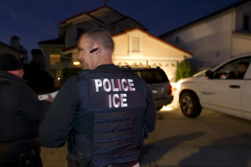 In this March 30, 2012 photo, an Immigration and Customs Enforcement (ICE) agent waits with other agents outside of the home of a suspect before dawn as part of a nationwide immigration sweep in San Diego. Federal officials say they arrested more than 3,100 immigrants convicted of serious crimes and fugitives in a six-day nationwide sweep. Officials at U.S. Immigration and Customs Enforcement say the sweep included every state and involved more than 1,900 of the agency's officers and agents.  (AP Photo/Gregory Bull)