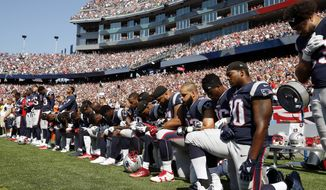 In this Sept. 24, 2017, file photo, several New England Patriots players kneel during the national anthem before an NFL football game against the Houston Texans in Foxborough, Mass. (AP Photo/Michael Dwyer) ** FILE **